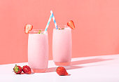 istock Strawberry smoothie in glass with straw and scattered berries on pink background. 1140113368