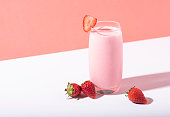istock Strawberry smoothie in glass with straw and scattered berries on pink background. 1140113373