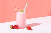 istock Strawberry smoothie in glass with straw and scattered berries on pink background. 1143563854