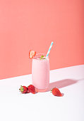 istock Strawberry smoothie in glass with straw and scattered berries on pink background. 1149097082