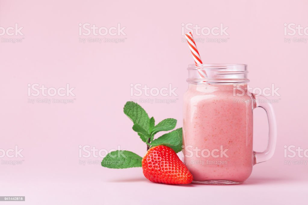 Strawberry smoothie or milkshake in mason jar decorated mint on pink table. Healthy food for breakfast and snack. stock photo