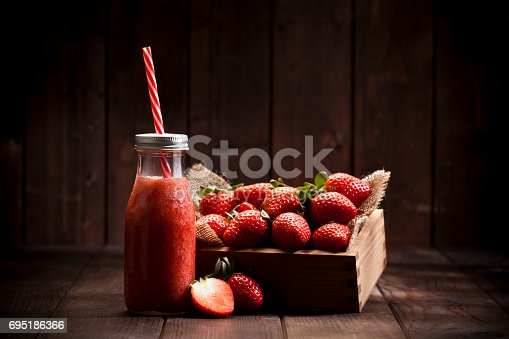 Horizontal shot of a strawberry smoothie in a glass bottle with a red and white drinking straw on rustic wood table. A small wooden crate filled with strawberries is at the right of the bottle and some fruits are out of the crate. Predominant colors are red and brown. Low key DSRL studio photo taken with Canon EOS 5D Mk II and Canon EF 70-200mm f/2.8L IS II USM Telephoto Zoom Lens