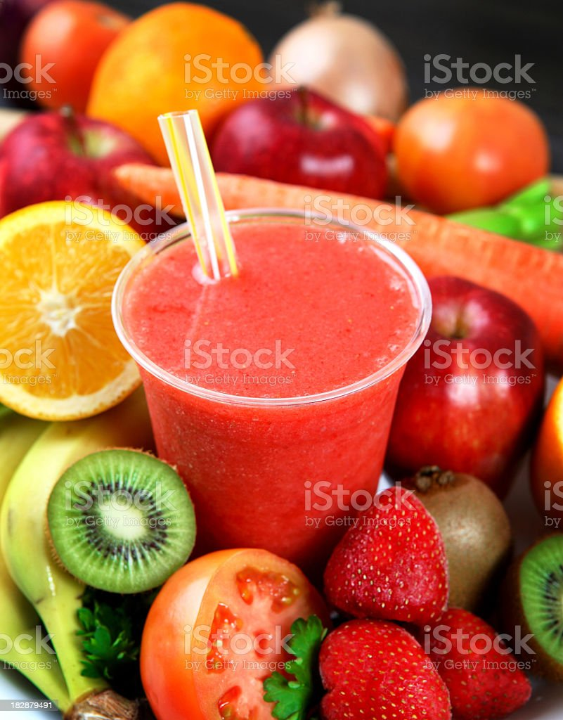 A strawberry smoothie surrounded by fruits stock photo