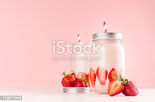 Strawberry smoothie in retro glass jar with bright sliced berries, straw and silver lid on light, soft, pink background, copy space.