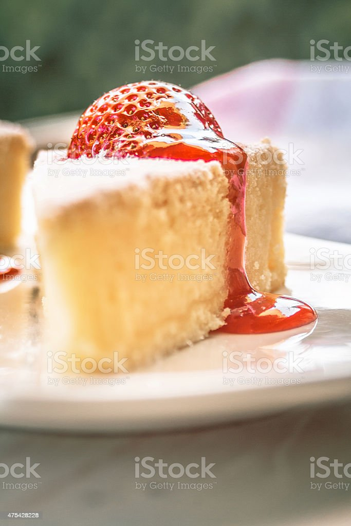 Strawberry syrup pouring down the cheesecake stock photo
