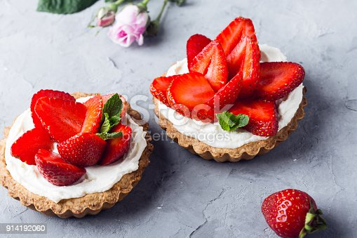 Strawberry tarts with  custard, delicious holiday fruit dessert over light gray background
