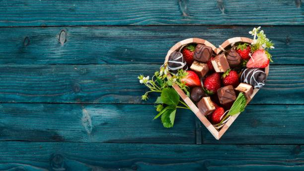 Strawberry with chocolate in a wooden box. On a wooden background. Top view. Copy space. Strawberry with chocolate in a wooden box. On a wooden background. Top view. Copy space. chocolate fondue stock pictures, royalty-free photos & images