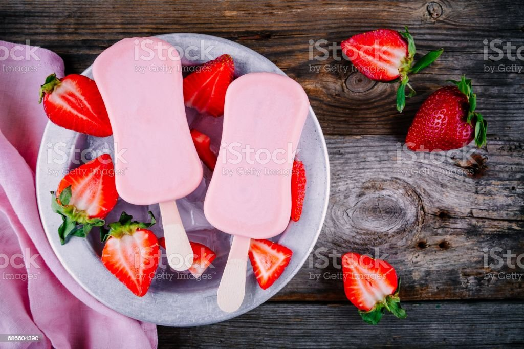 Strawberry yogurt ice cream popsicles with fresh berries royalty-free stock photo