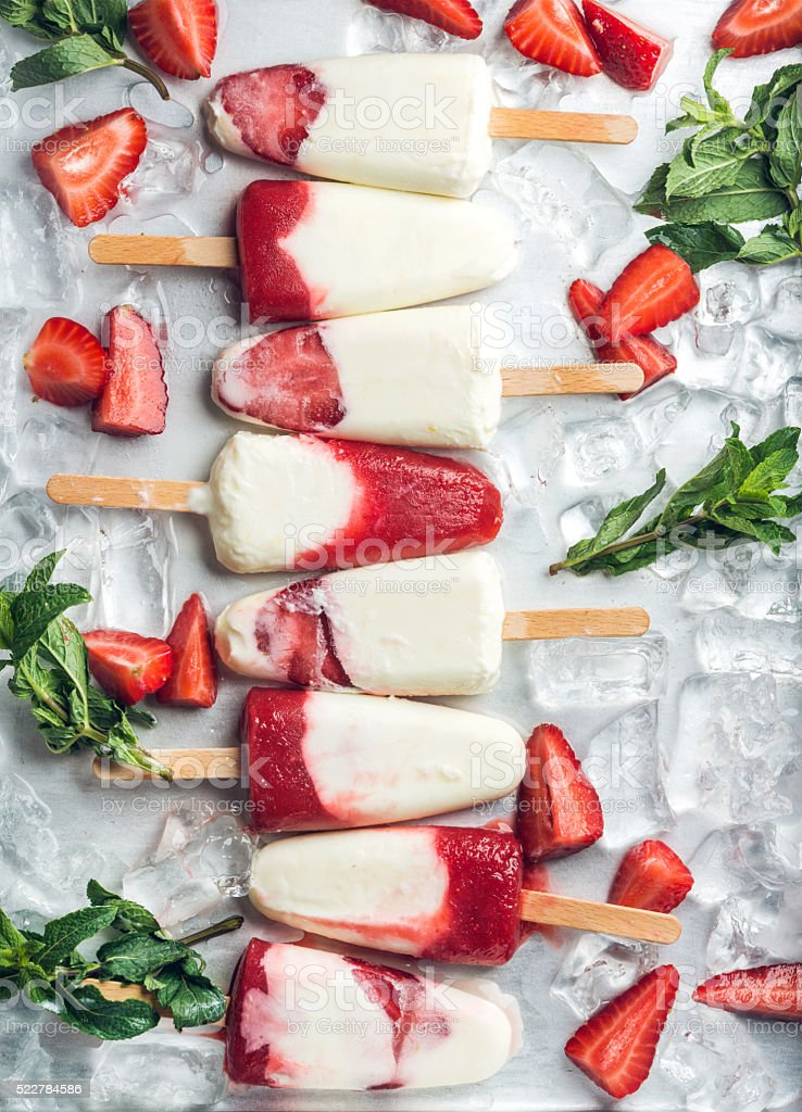 Strawberry yogurt ice cream popsicles with mint stock photo