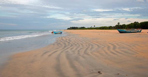 Streaky patterns in sand with boat on Nilaveli beach in Sri Lanka Asia stock photo