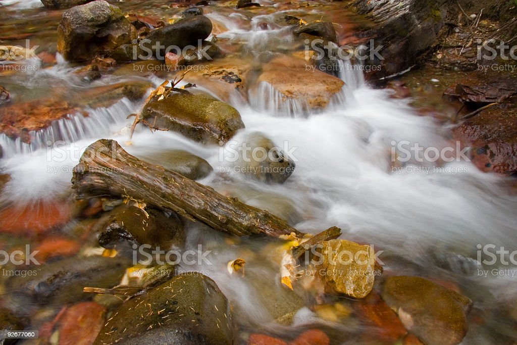 Stream cascading over rocks and autumn leaves royalty-free stock photo