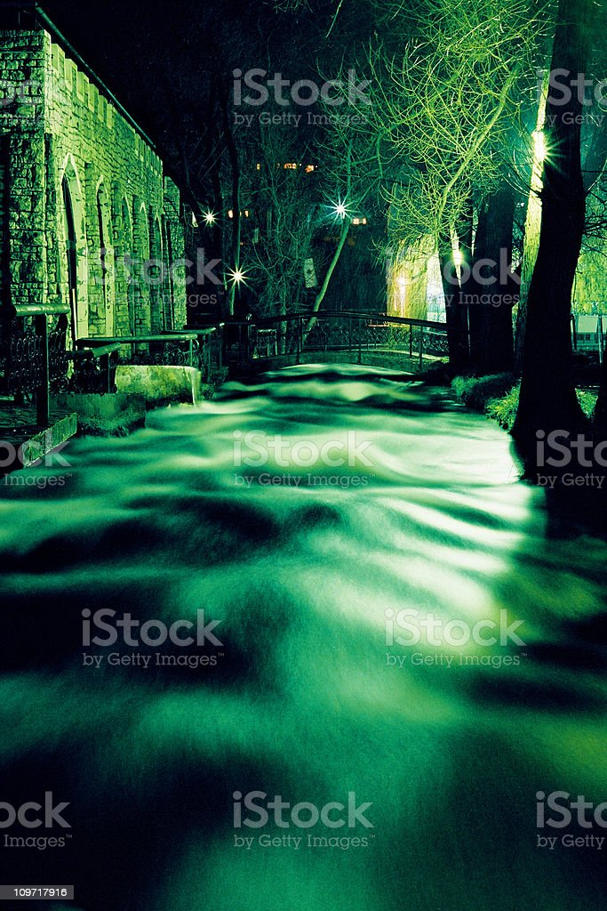 Stream Flowing Under Bridge at Night stock photo