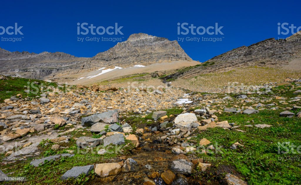 Stream Flows Off Mountain Side Stream Flows Off Mountain Side in Montana mountains Agricultural Field Stock Photo