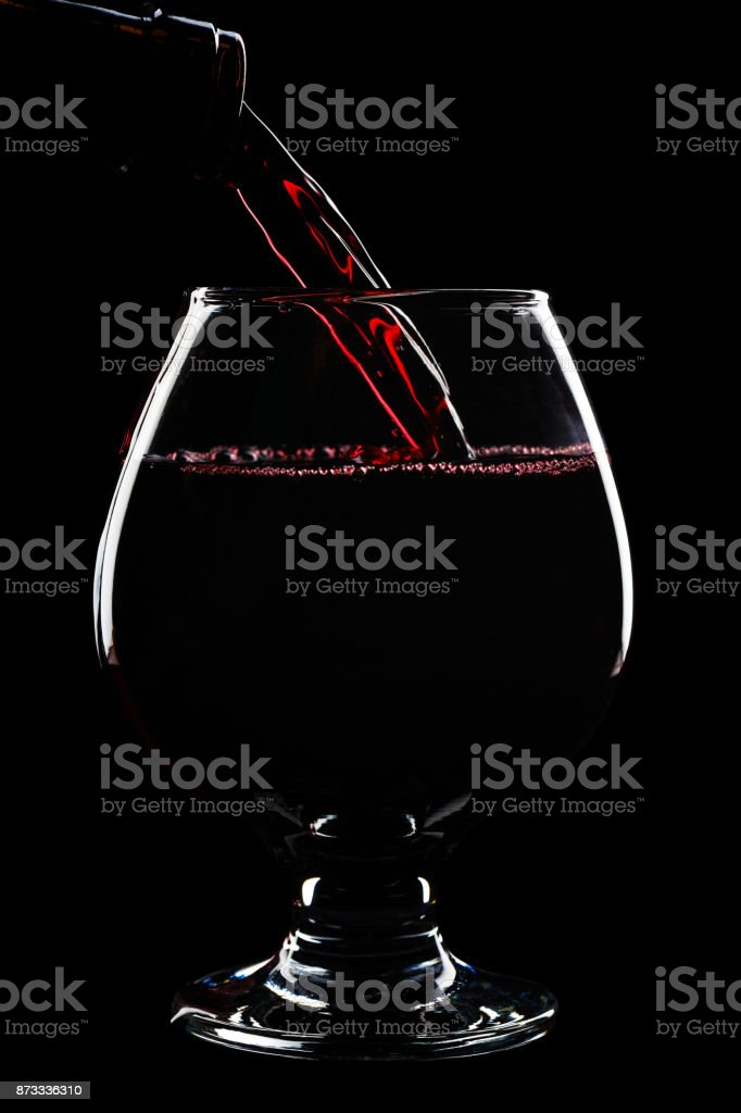 Stream of red wine pours into the wine glass stock photo