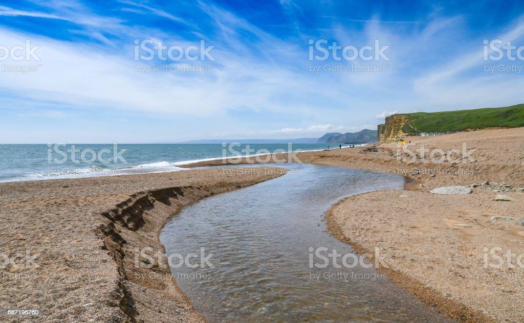 Stream to the sea at West Bay coastline in Dorset, England stock photo