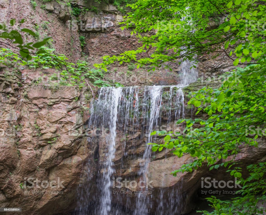 Stream waterfall cascading from the cliff. stock photo