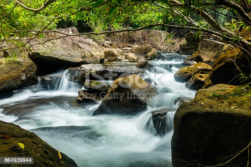 Below Khlong Chao waterfall on Koh Kood island, Thailand, the clean stream of water rushes among the boulders and lush foliage of the tropical forest.