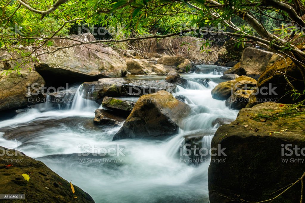 Stream with boulders and tropical forest in Koh Kood, Thailand stock photo