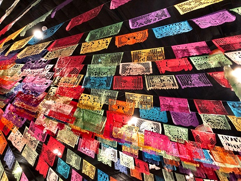 Lines of colorful flags with Mexican themes of celebration.