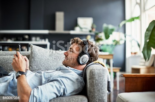 Cropped shot of a handsome young man listening to music on his mobile phone at home