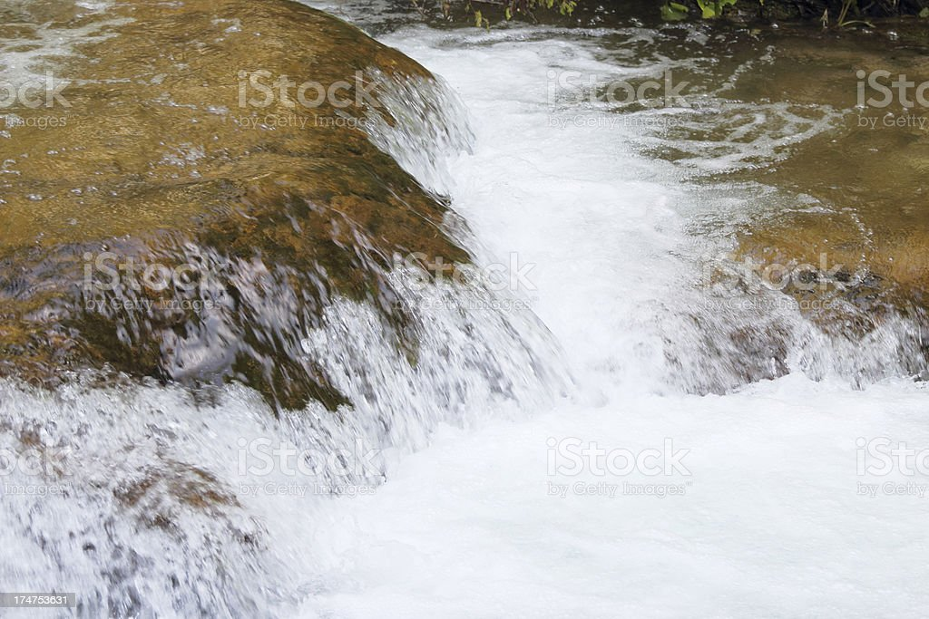 streaming water cascade detail with brown rocks Plitvice Lakes Croatia royalty-free stock photo
