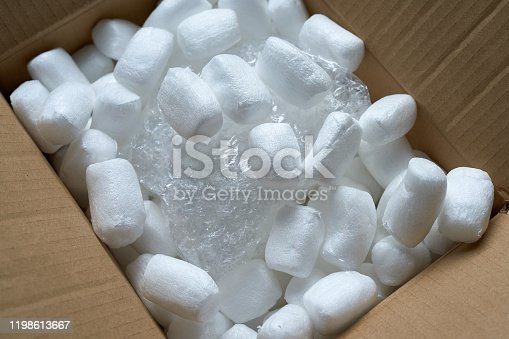 Streamlined polystyrene pieces inside the mail package. Foam filler is a reliable way to pack items. Bulk - for the safe transportation of goods. The package is open. Polyethylene depreciation wrap.