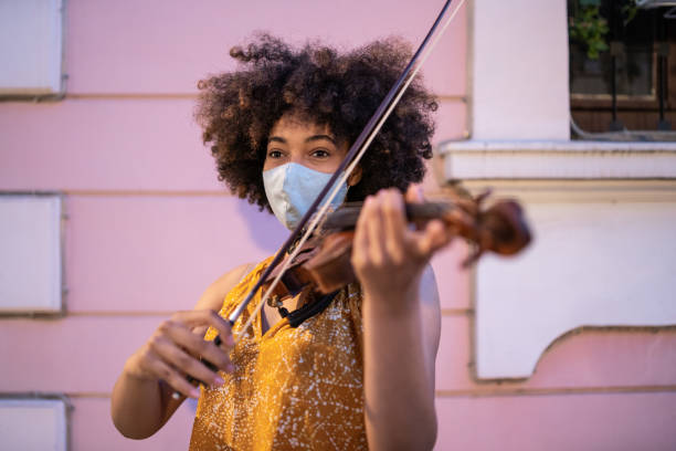 street afro musician playing violin and wearing protective face mask, during covid-19 - afro latino mask imagens e fotografias de stock