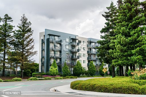 Street and apartment building surrounded by redwood trees; overcast day; San Jose, San Francisco bay area, California