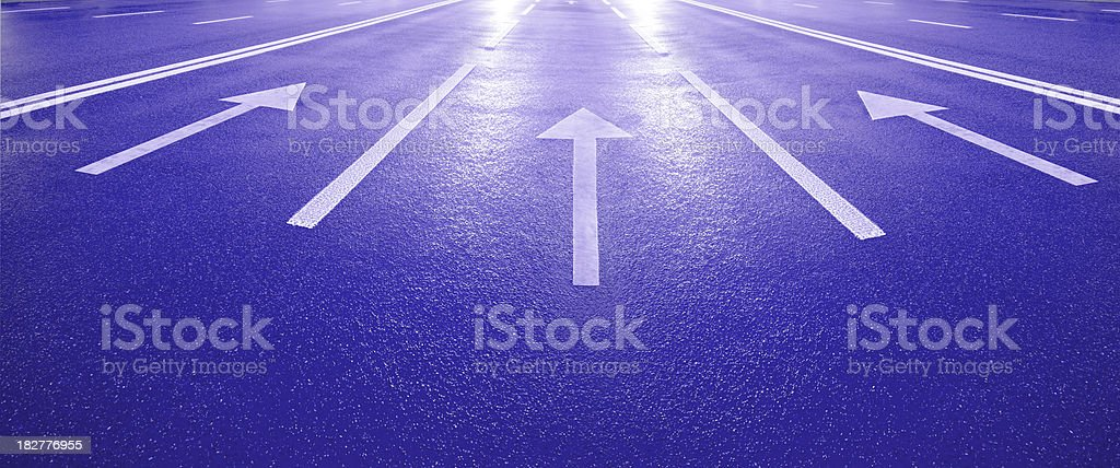 Street arrows pointing into the bright light stock photo