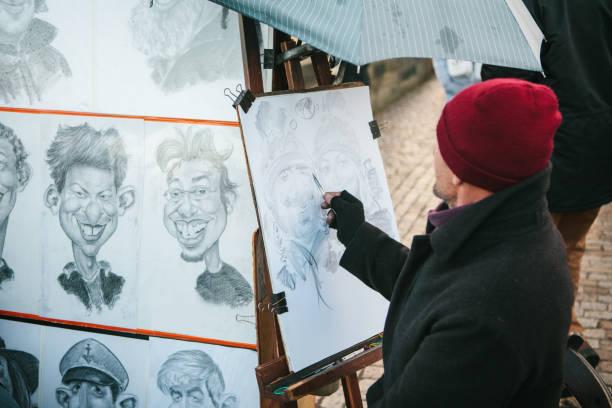 streetart-künstler karikaturist in eine rote mütze zeichnet porträts für touristen in prag - karikatur stock-fotos und bilder