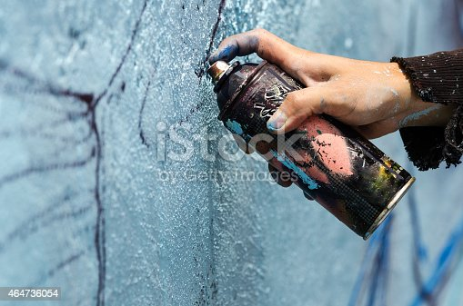 A young man holds a dark can of spray paint close to a blue wall to sketch his graffiti.
