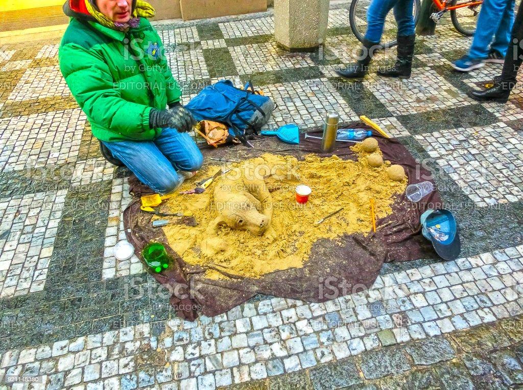 A street artist making a sand sculpture of dog stock photo