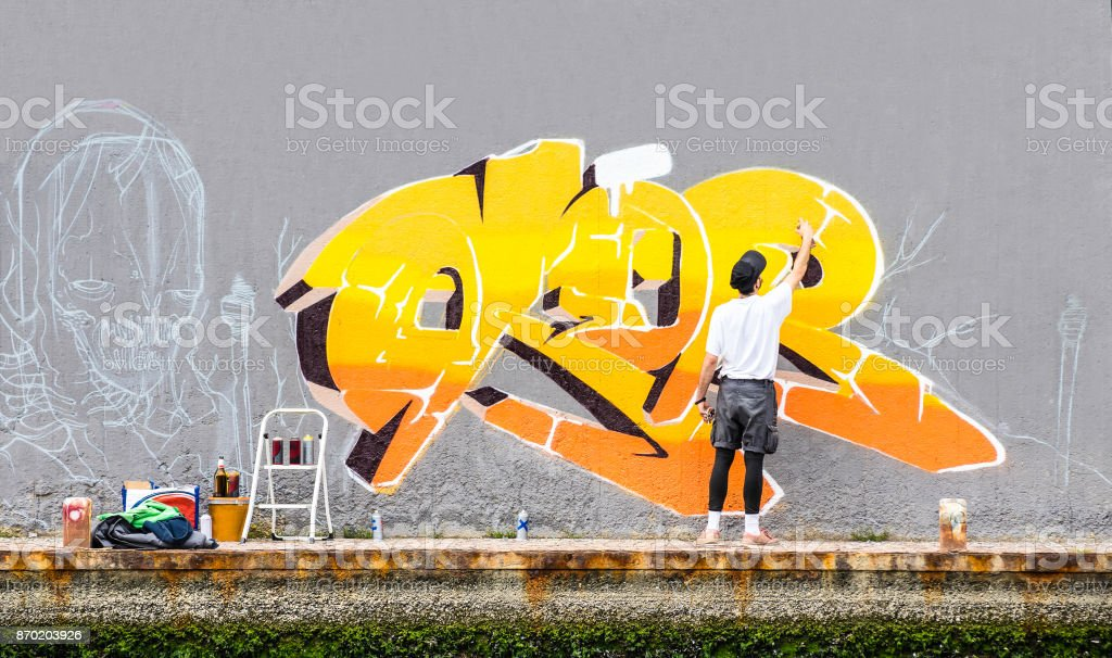 Street artist painting colored graffiti on public space wall - Modern art concept of urban guy performing and preparing live murales paint with yellow aerosol color spray - Cloudy afternoon filter stock photo
