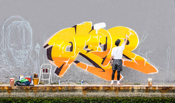 street artist painting colored graffiti on public space wall - modern art concept of urban guy performing and preparing live murales paint with yellow aerosol color spray - cloudy afternoon filter - berlin wall imagens e fotografias de stock