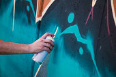 Street artist painting colorful graffiti on generic wall - Modern art concept with urban guy performing and preparing live murales with multi color aerosol spray