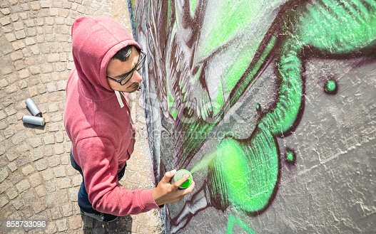 istock Street artist painting colorful graffiti on generic wall - Modern art concept with urban guy performing and preparing live murales with green aerosol color spray - Sunny afternoon neutral filter 858733096