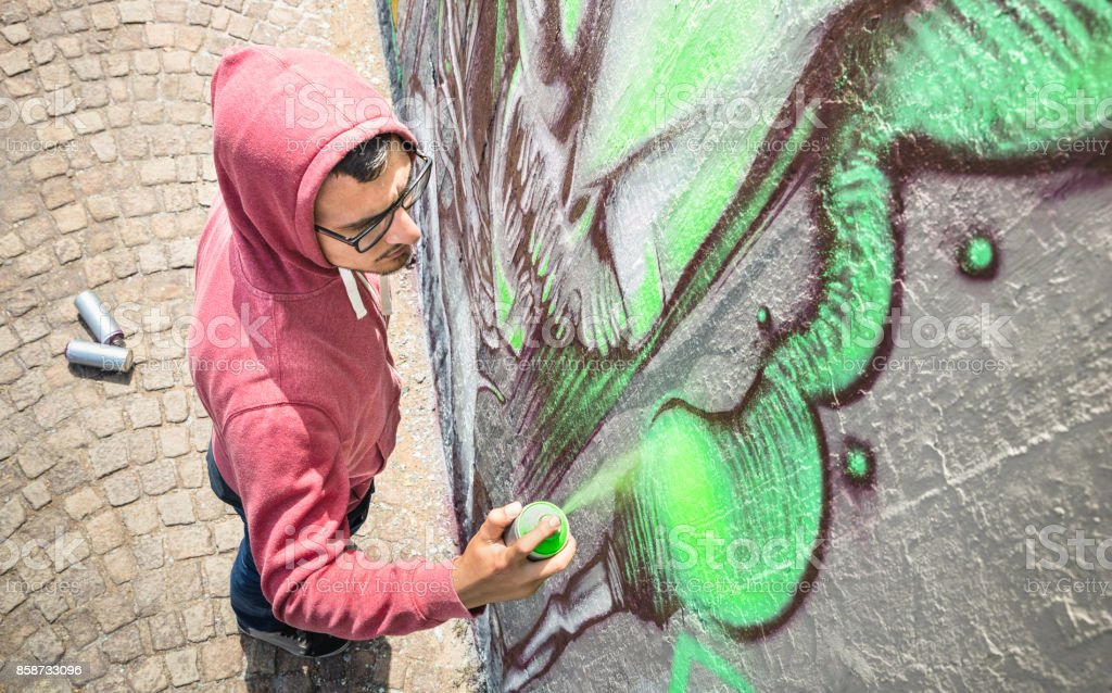 Street artist painting colorful graffiti on generic wall - Modern art concept with urban guy performing and preparing live murales with green aerosol color spray - Sunny afternoon neutral filter stock photo