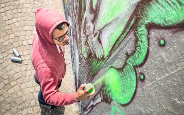 ジェネリックのストリート アーティスト絵画カラフルな落書き壁 - 都市の男を実行してグリーン カラー スプレーとライブ題材を準備と現代アート コンセプト - 日当たりの良い午後中立的なフィルター - street graffiti ストックフォトと画像