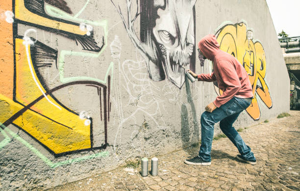 street artist painting colorful graffiti on generic wall - modern art concept with urban guy performing and preparing live murales with multi color aerosol spray - contrast retro vintage filter - berlin wall imagens e fotografias de stock