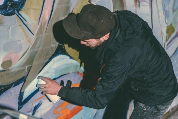 calle artista pintura colorido graffiti en pared de edificio en la noche - foto de stock