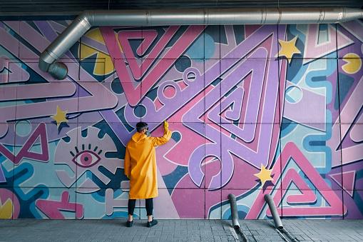Street artist painting colorful graffiti on wall Modern art, urban concept.