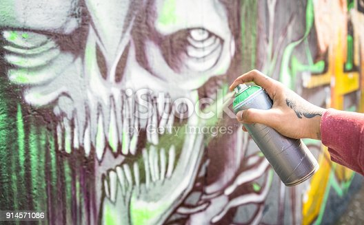 istock Street artist painting colorful monster graffiti on public wall - Modern art concept with urban guy performing and preparing live murales with multi color aerosol spray - Focus on hand 914571086