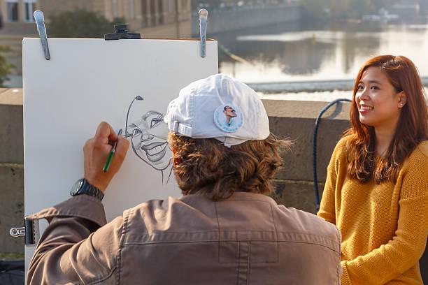 Street artist paints a portrait-caricature of a beautiful girl stock photo