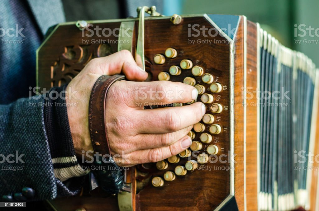 A street artist playing bandoneon, traditional tango instrument, on Caminito street in La Boca neighborhood, Buenos Aires stock photo