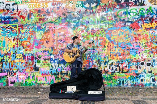 Prague, Czech Republic - June 27, 2016: Street artist playing guitar at the famous Lennon graffiti wall in old town of Prague, Czech Republic