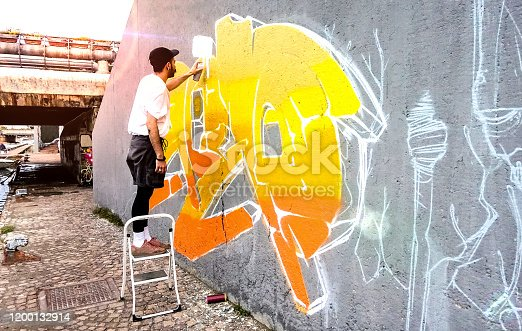 185278362 istock photo Street artist working on colored graffiti at public space wall - Modern art perform concept of urban guy painting live murales with yellow and orange aerosol color spray - Bright sunflare filter 1200132914