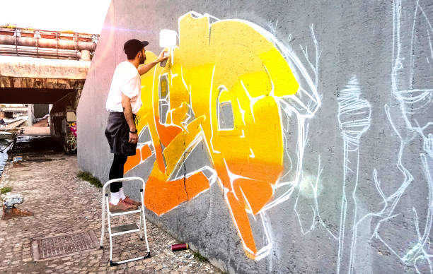 Street artist working on colored graffiti at public space wall - Modern art perform concept of urban guy painting live murales with yellow and orange aerosol color spray - Bright sunflare filter stock photo