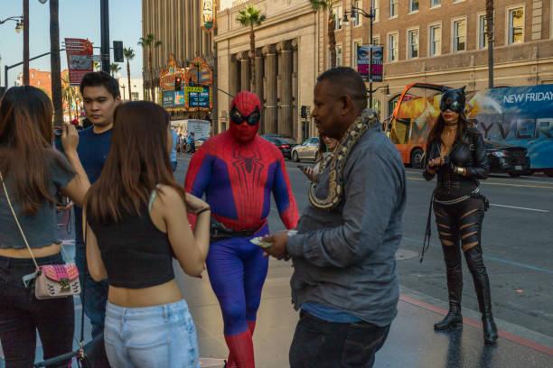 straßenkünstler und touristen, die auf dem hollywood boulevard spazieren gehen - oscar filme stock-fotos und bilder
