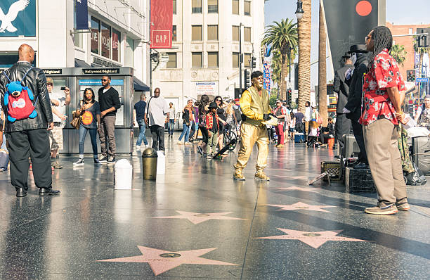 Street artists on the Walk of Fame in Hollywood Los Angeles, United States - March 21, 2015: street artists and everyday multiracial people around the world famous Walk Of Fame in late afternoon on Hollywood Boulevard in LA California - United States of America hollywood boulevard stock pictures, royalty-free photos & images