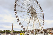Paris, FRANCE - May 08, 2017: with a gray and threatening sky in Paris, France, street atmosphere on the Place de la Concorde with its Ferris wheel and Hotel Crillon